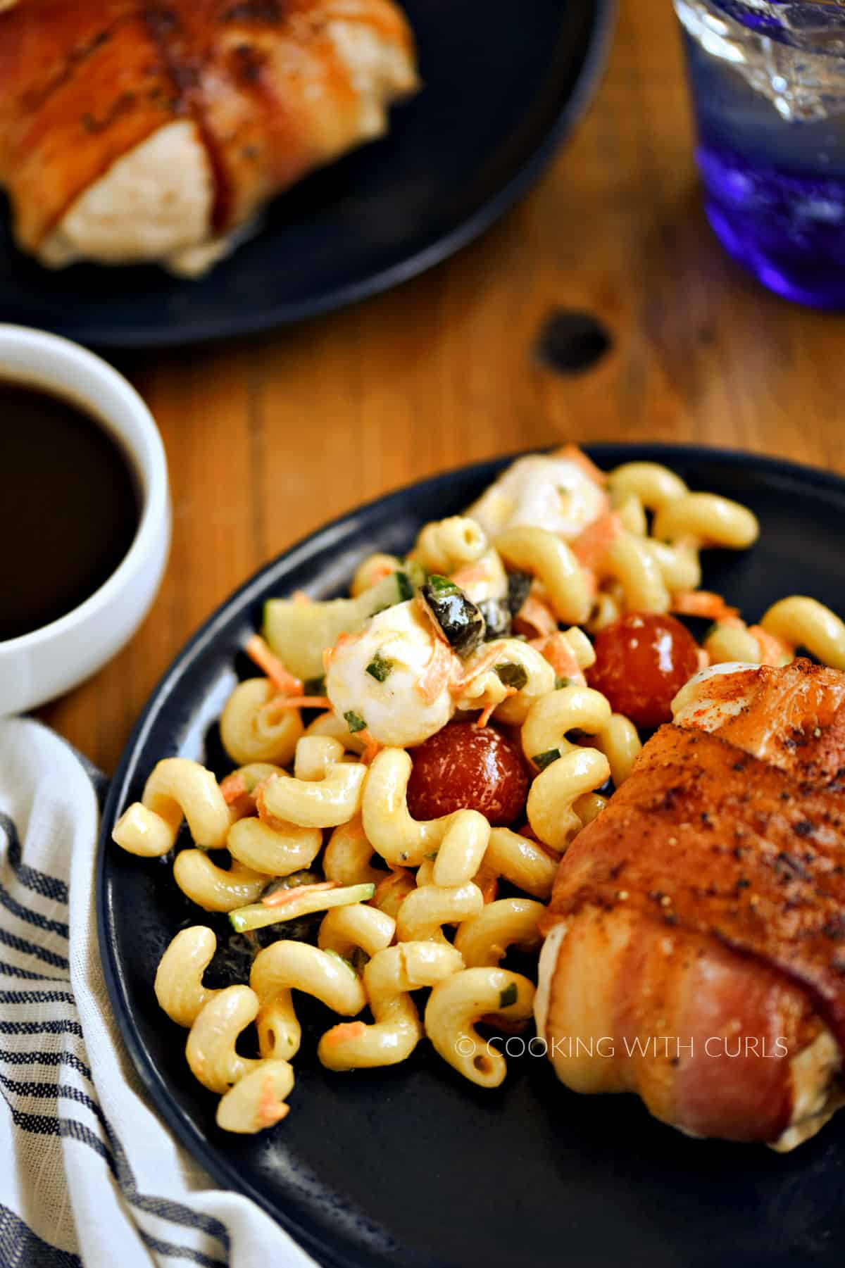 Italian Pasta Salad with bacon wrapped chicken breast on a blue plate.