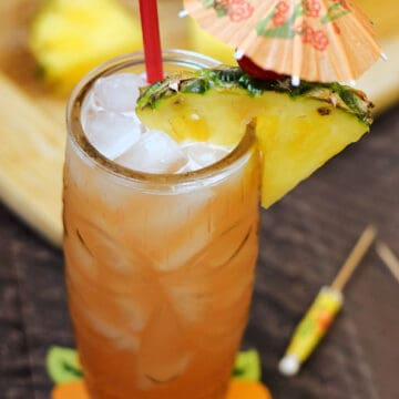 Orange cocktail in a tiki glass with a pineapple wedge, cherry, red straw and orange paper umbrella.