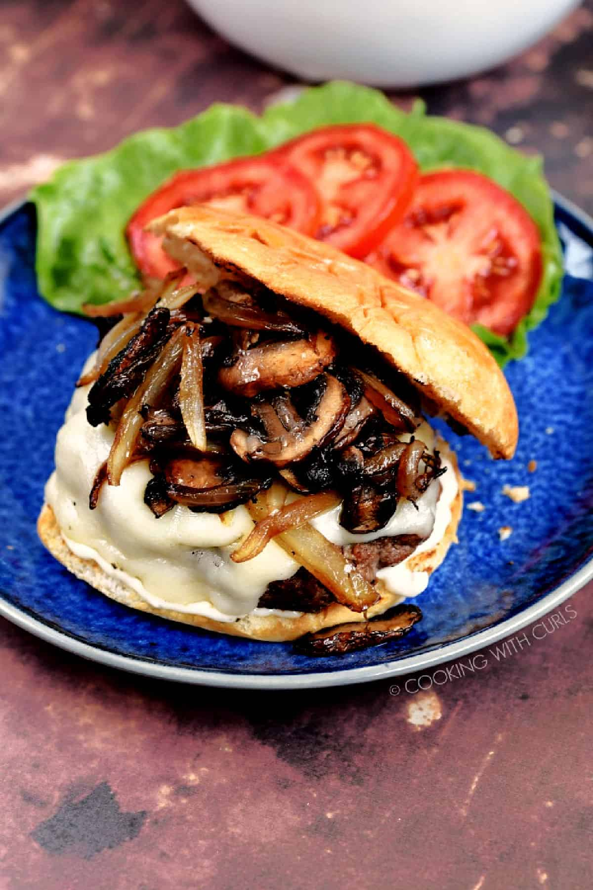 Mushroom Swiss Burgers on a blue plate with lettuce and tomato on the side.