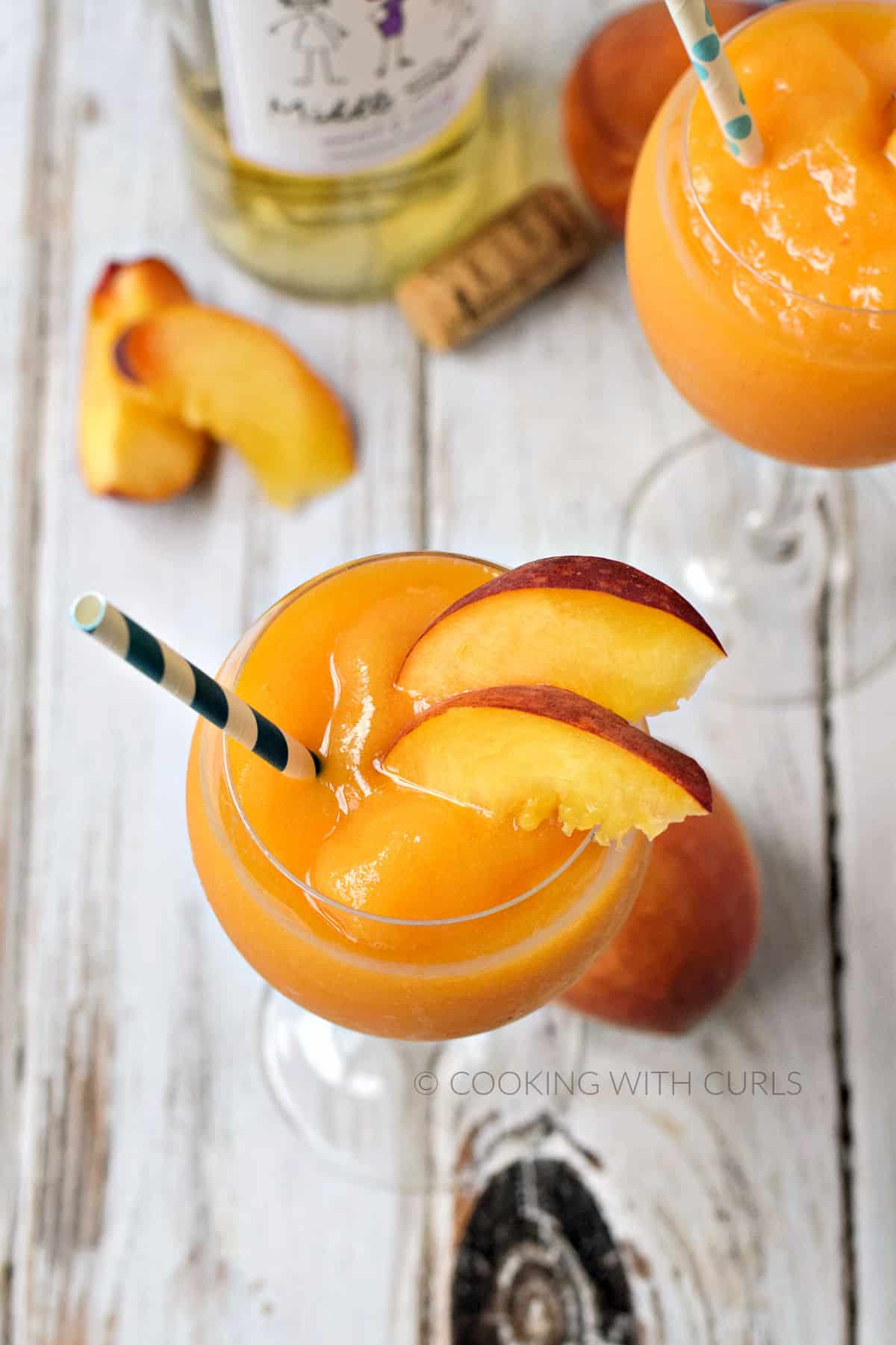 Looking down on two wine glasses filled with blended peaches and wine smoothie garnished with peach slices and a bottle of white wine in the background.