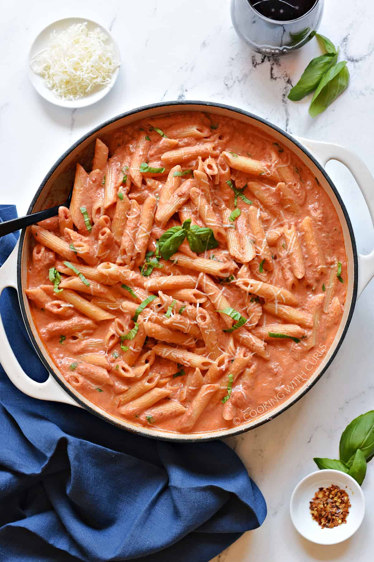 Penne tossed in a creamy tomato sauce topped with grated cheese and fresh basil in a large skillet.
