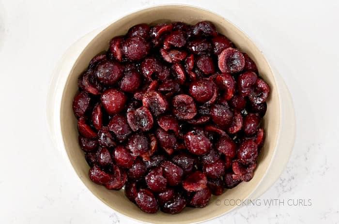 Prepared cherry halves in a round baking dish.