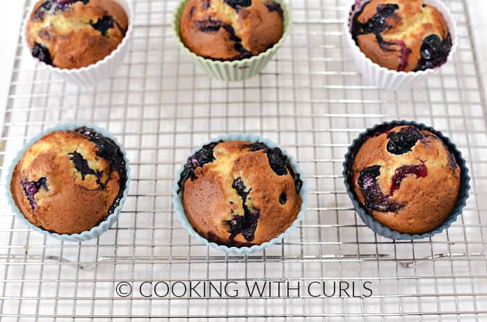 Six blueberry muffins on a wire cooling rack.