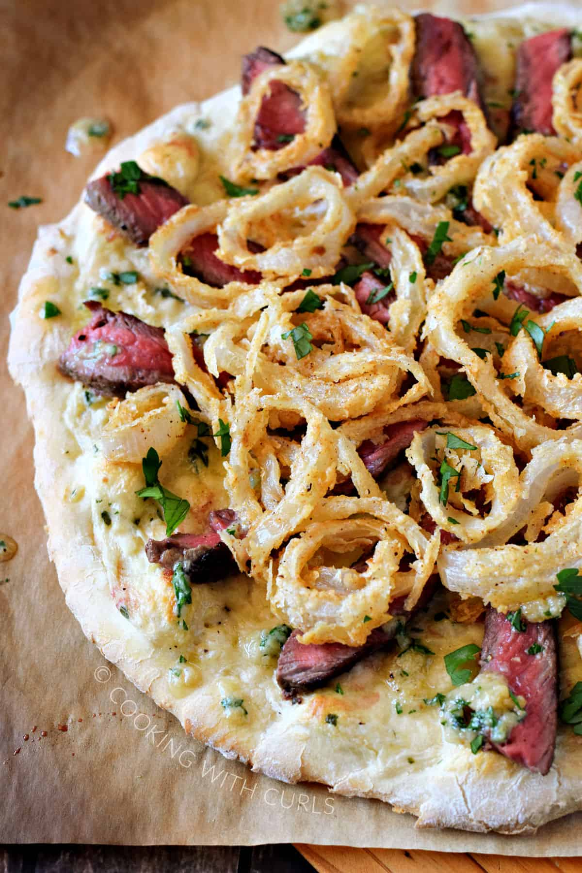 Pizza topped with white pizza sauce, strips of medium-rare steak, Gorgonzola butter, and crispy onion rings.