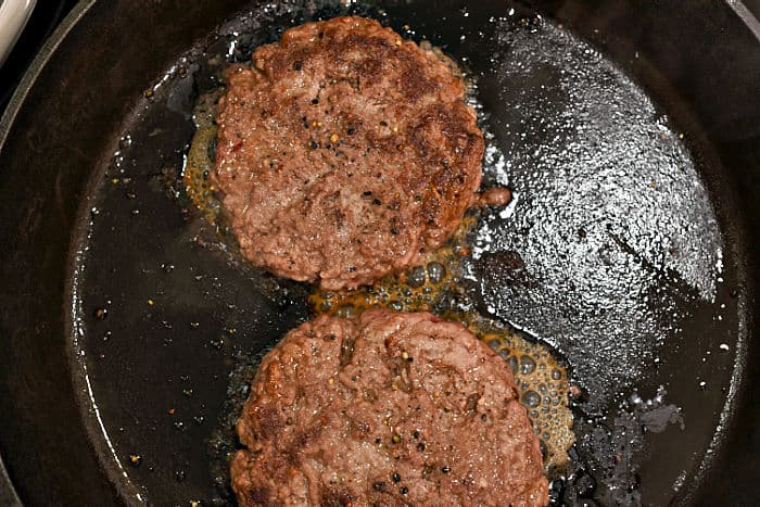 Two burger patties in a cast iron skillet.