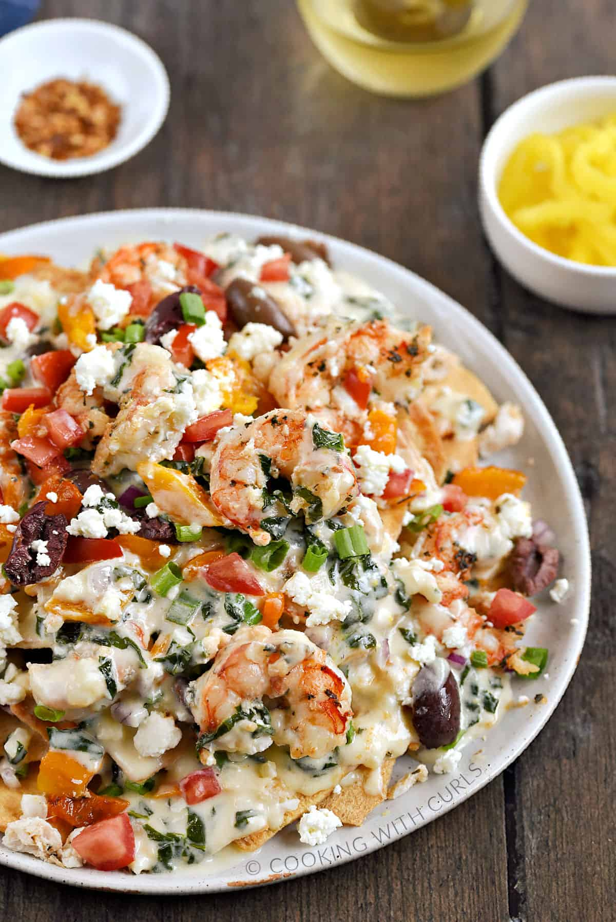 A large plate topped with shrimp, crab, diced tomatoes, olives, orange peppers, green onions, pita chips, and spinach cheese sauce.