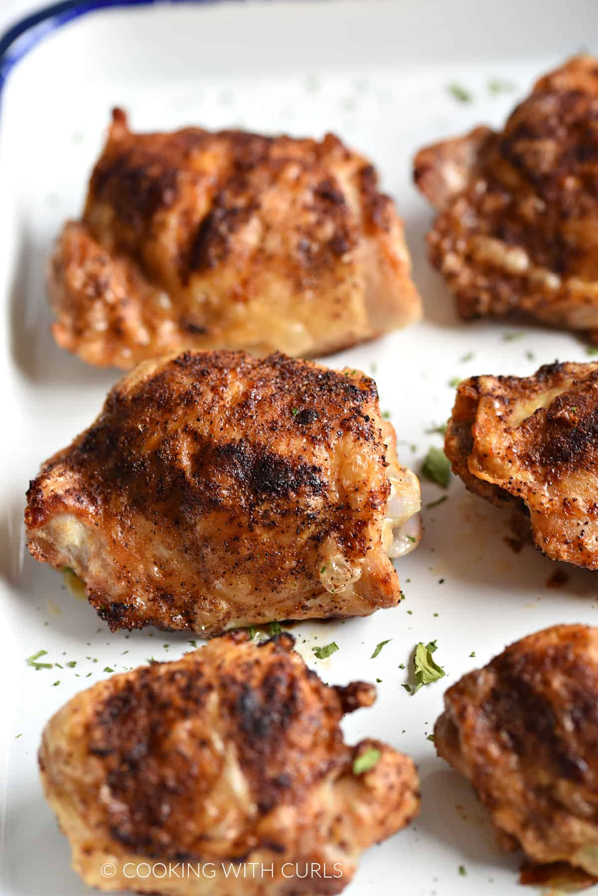 Close up image of six crispy chicken thighs on a white platter.