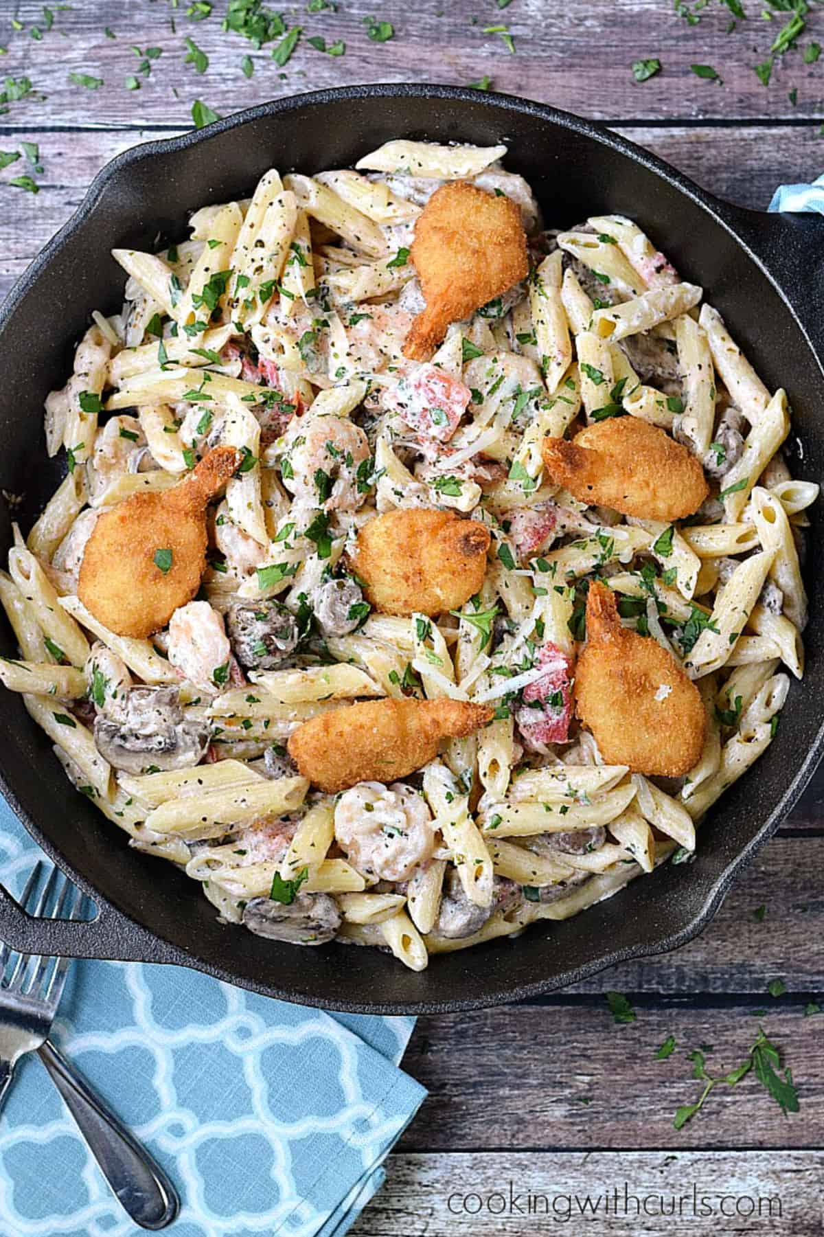 Looking down on a cast iron skillet filled with penne pasta, creamy sauce, tomatoes, mushrooms, and breaded shrimp.