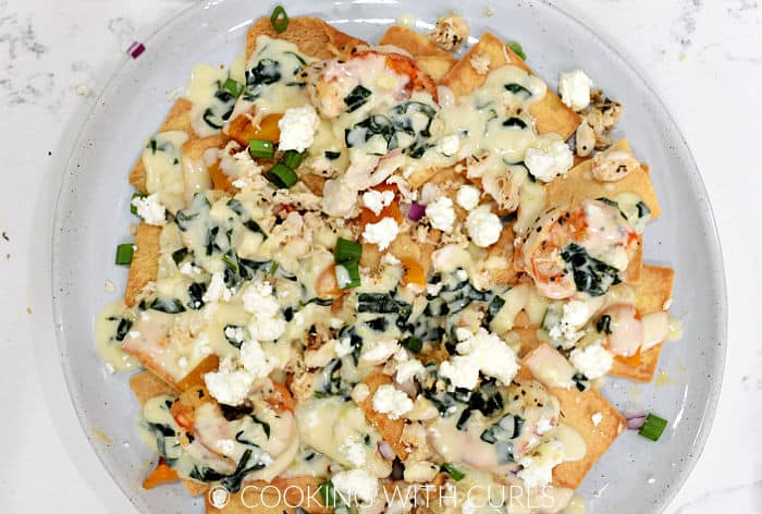 First layer of pita chips, spinach cheese sauce, orange pepper, diced onion, shrimp, and feta cheese crumbles on a large plate.