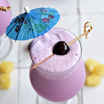 Frozen pink cocktail with blue umbrella and fresh cherry on a bamboo stick.