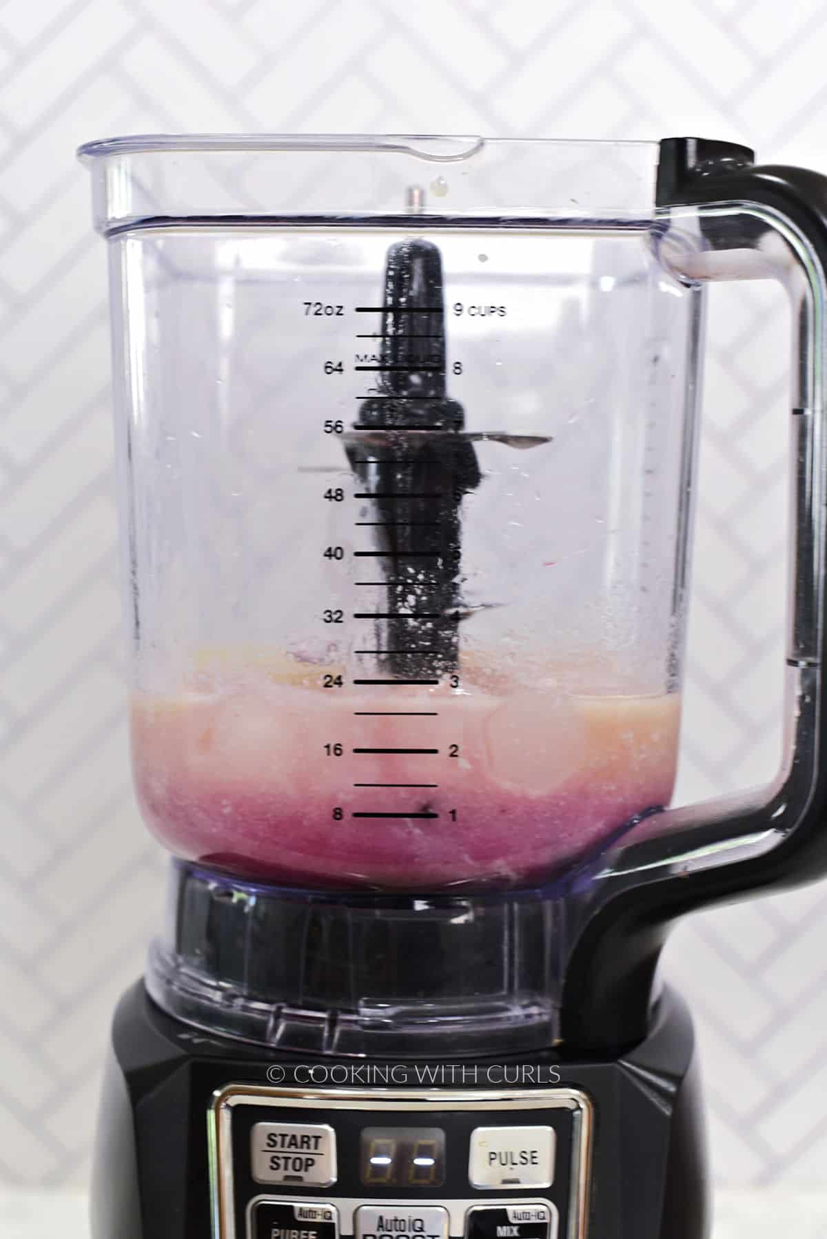 Fresh cherries, pineapple juice, coconut cream, heavy cream, ice cubes, and cherry syrup in a blender.