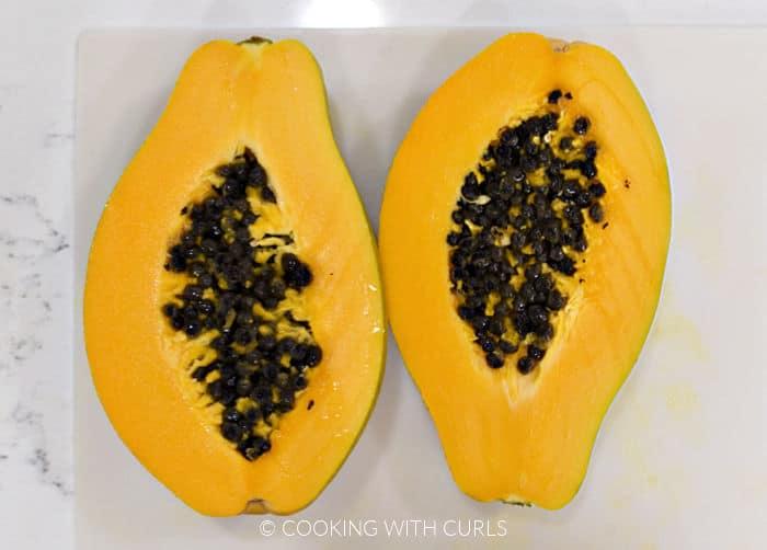 Fresh papaya sliced in half on a plastic cutting mat.