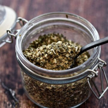 A small glass jar filled with Greek herbs and spices.