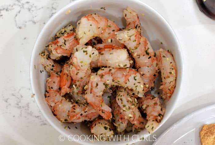 Large shrimp tossed with Greek seasoning in a small bowl.