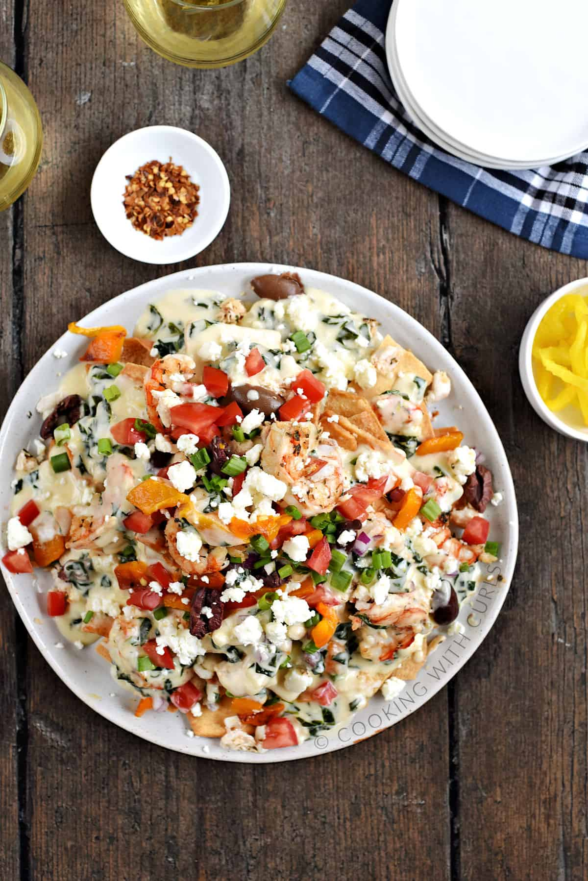 Looking down on a large plate of Greek Seafood Nachos with two glasses of white wine, a bowl of crushed red pepper, and a bowl of banana peppers in the background.