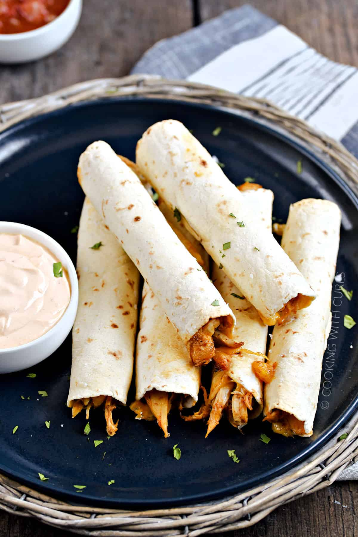 Looking down on six baked peachy chicken taquitos stacked on a plate with a side of creamy adobo sauce and salsa on the side.