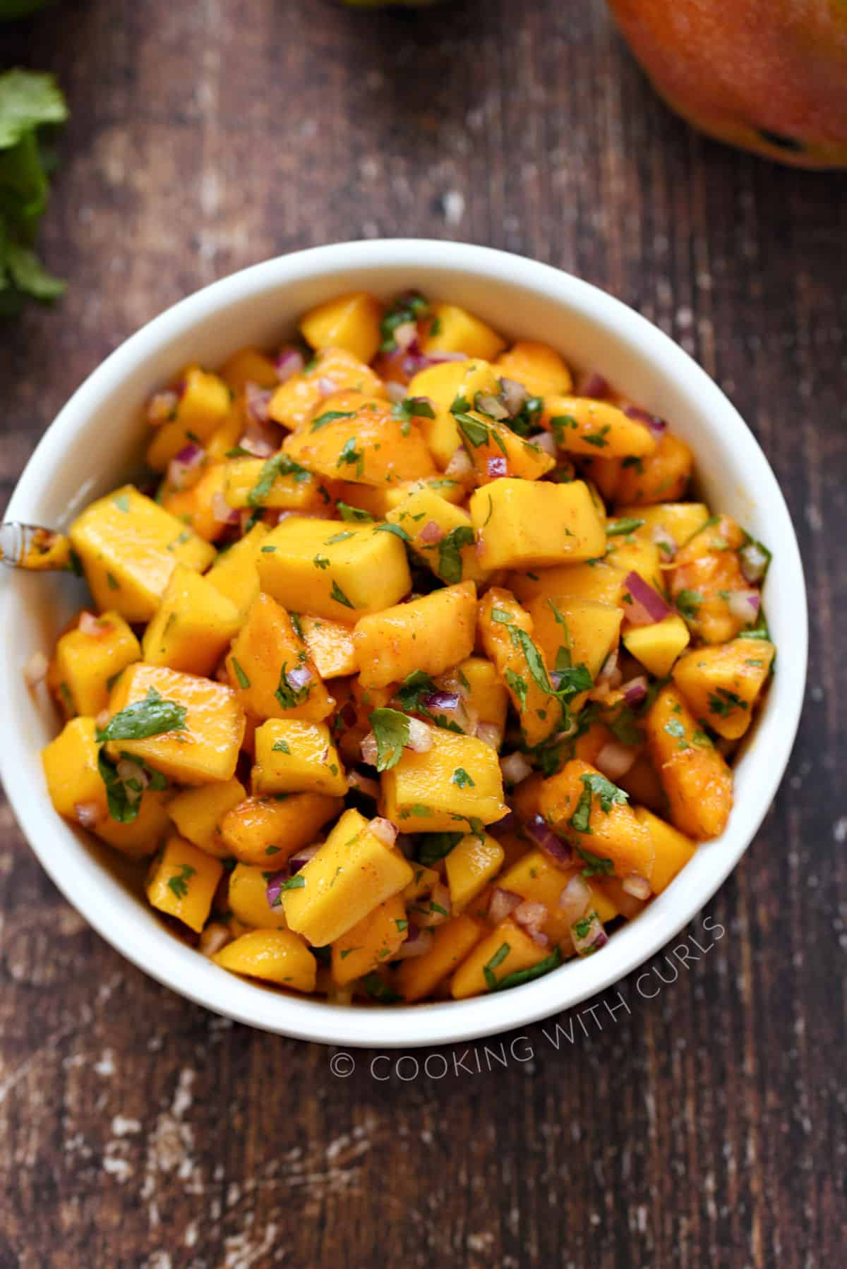 A small white bowl filled with chopped papaya, mango, red onion, cilantro, chipotle chili powder, and lime juice.