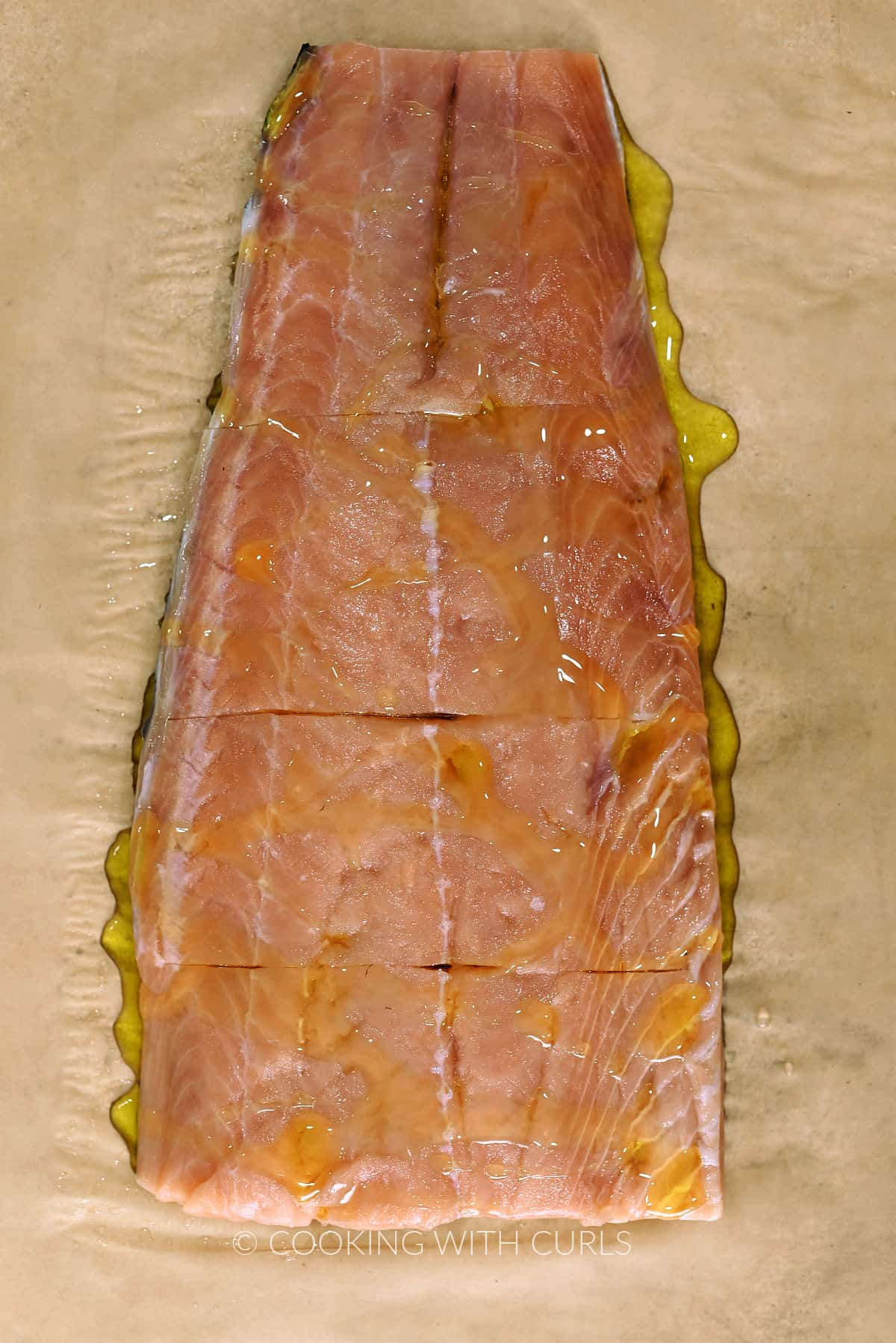 Salmon filet drizzled with olive oil on a parchment paper.