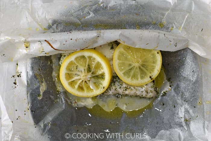 A baked cod filet in parchment paper opened up on a black plate.