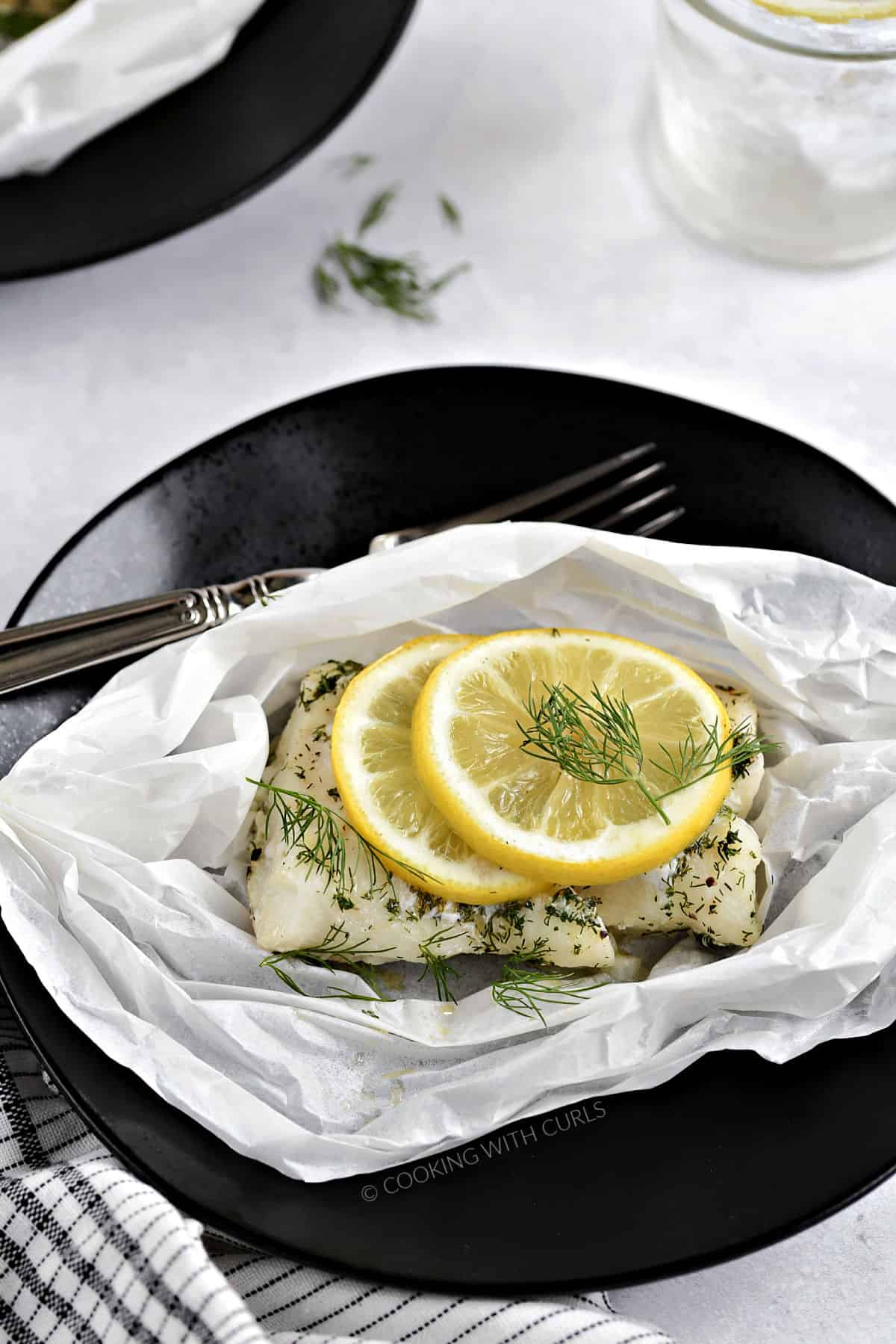 A cod filet topped with dill and a lemon slice in parchment paper sitting on a black plate.