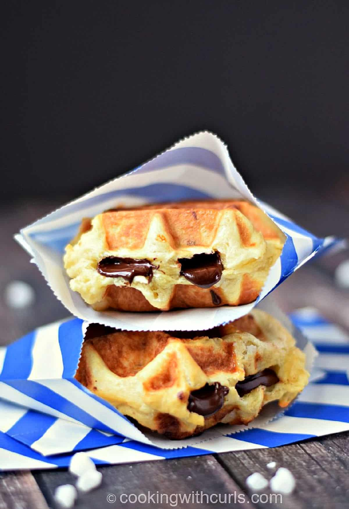 Two chocolate stuffed, thick waffles wrapped in blue and white striped paper envelopes and stacked on top of each other.