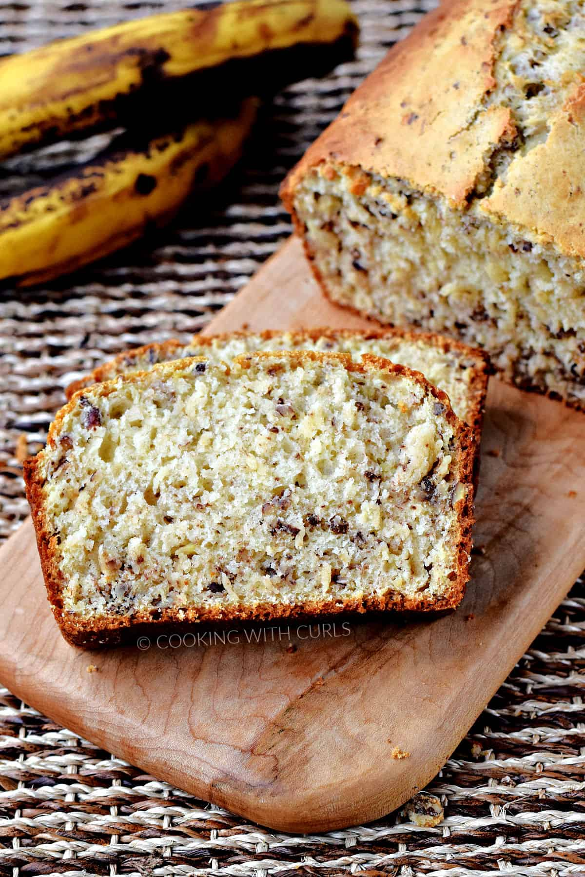 Two slices of banana nut bread on a board with the remaining loaf in the background and ripe bananas off to the side.