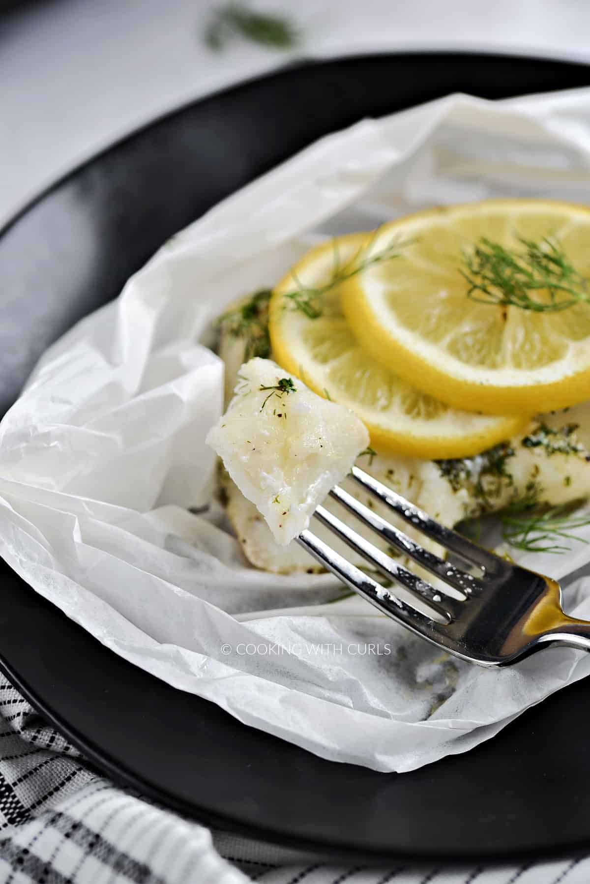 Flaky cod on a fork resting next to a lemon topped filet.