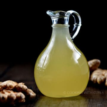 ginger syrup in a glass pitcher surrounded by ginger root.