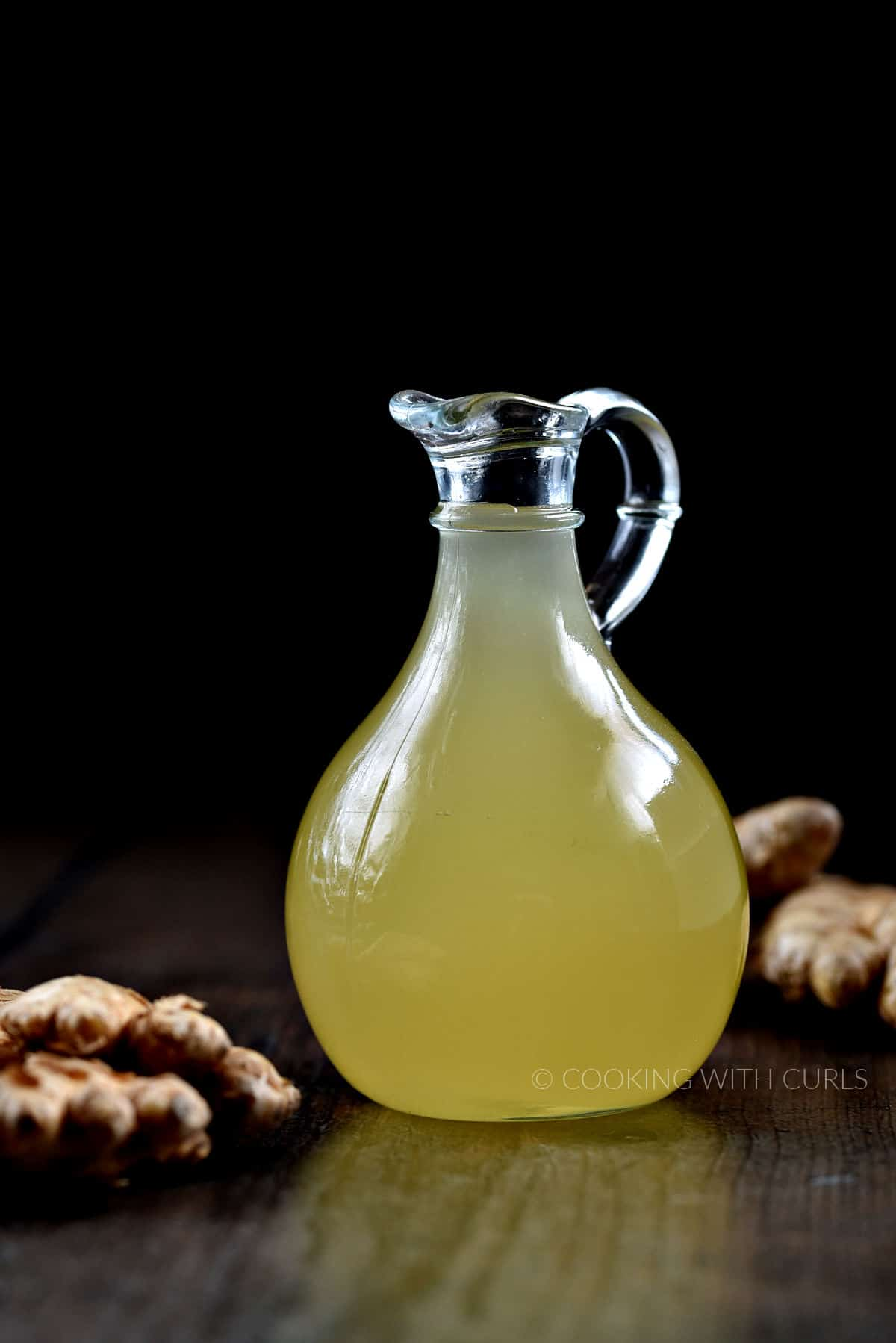 Ginger simple syrup in a glass jar with ginger root on the left  and right sides.