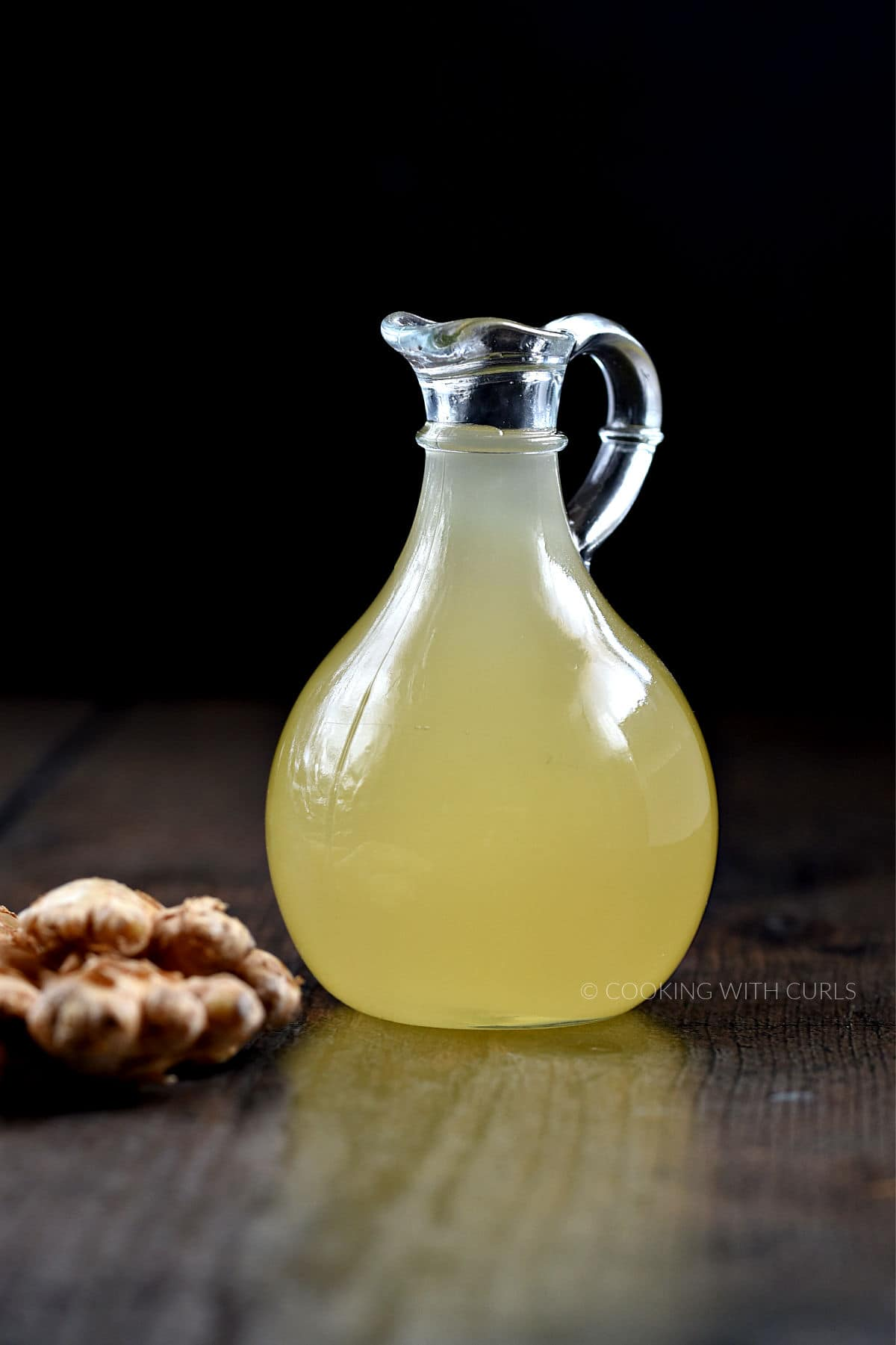 Ginger simple syrup in a glass jar with ginger root on the left side.