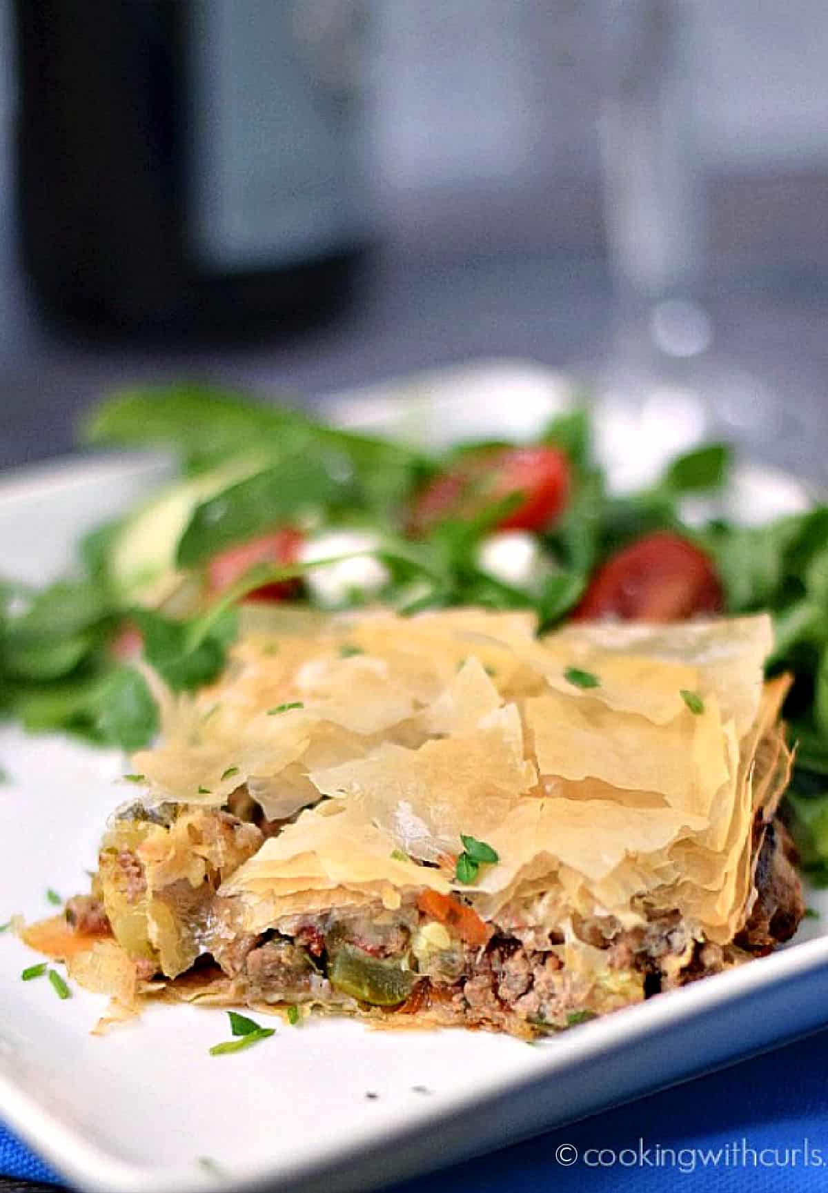 A slice of Greek Summery Meat Pie on a white plate with a Greek salad on the side.