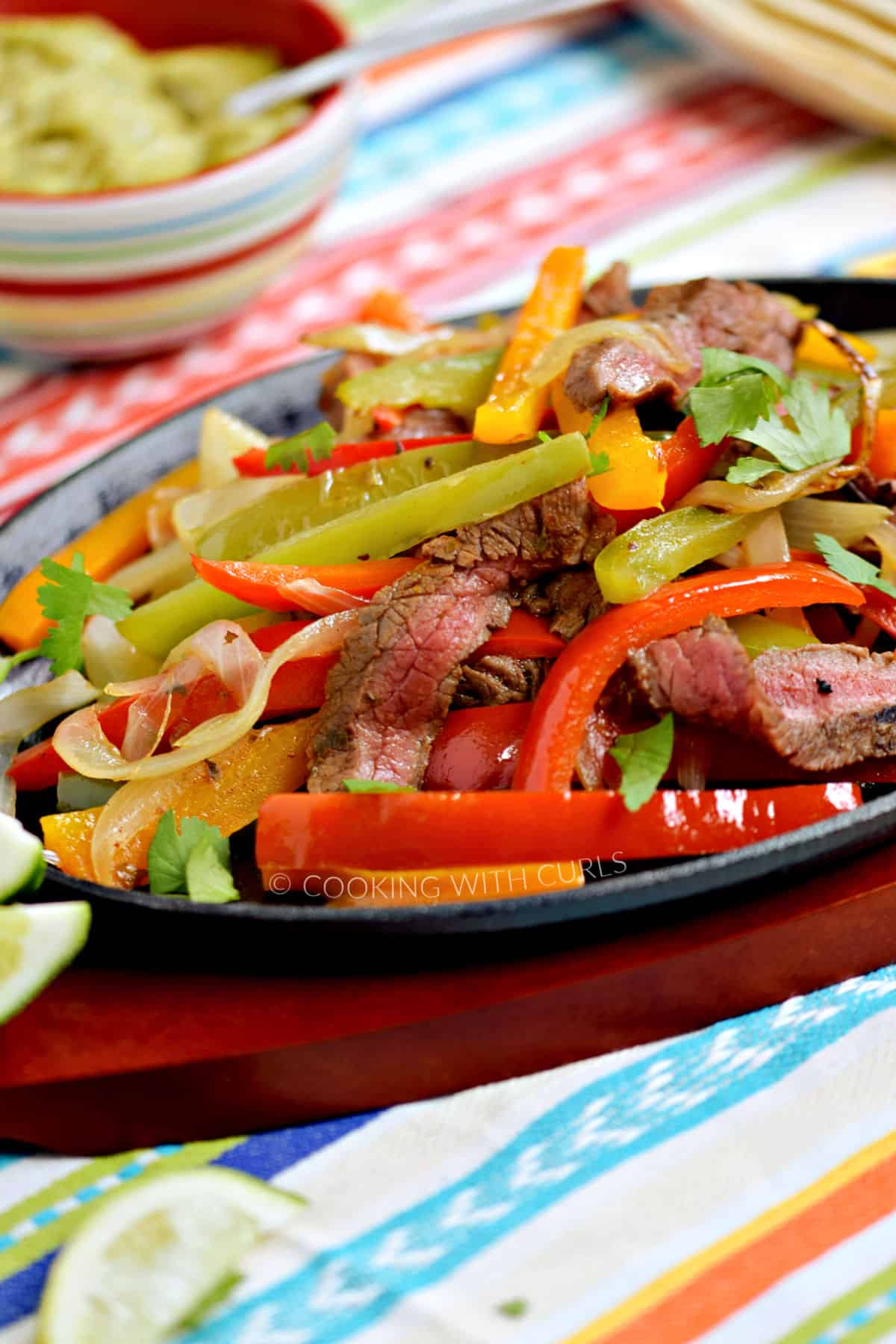 Strips of charred steak, bell peppers and onions in a fajita skillet surrounded by guacamole and salsa in small bowls.