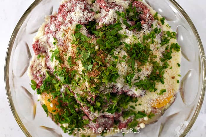 Ground beef, Parmesan cheese, parsley, eggs, and diced onions in a large bowl.