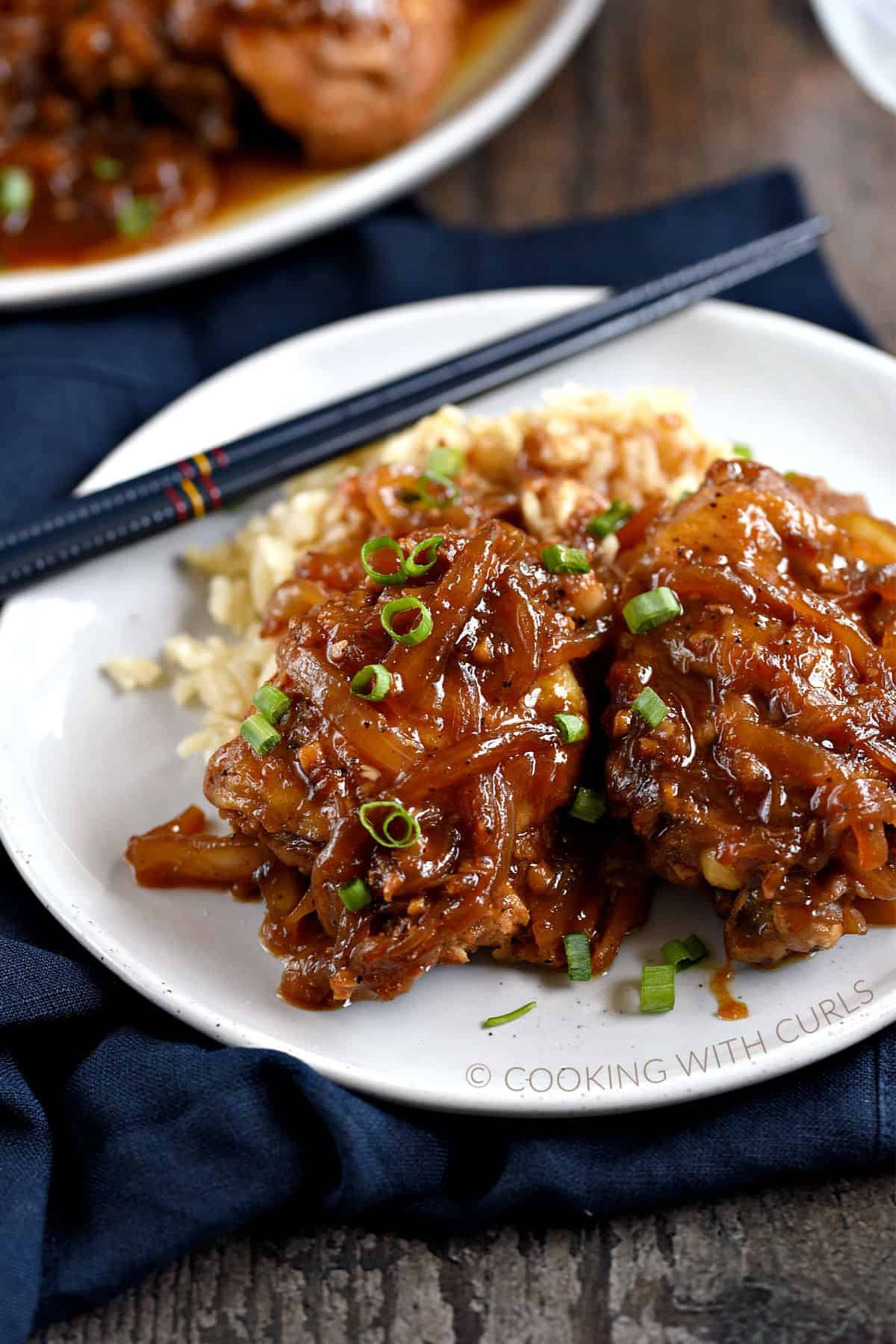 Two chicken thighs covered with a brown onion sauce and diced green onions on a bed of rice with chopsticks in the upper left corner of the plate.