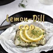 A cod filet topped with dill and a lemon slice in parchment paper sitting on a black plate with title graphic across the top.