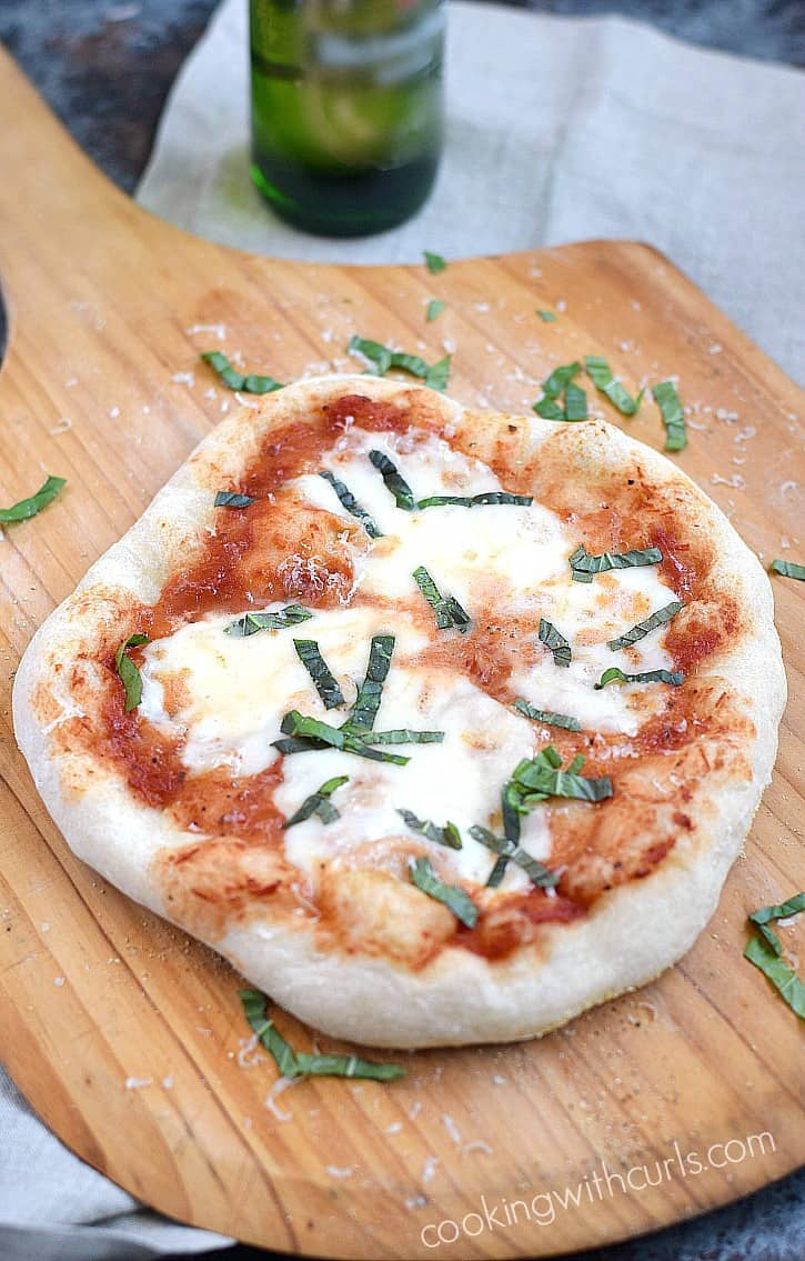 A puffy pizza crust topped with tomato sauce, melted mozzarella, and fresh basil on a wooden pizza peel.