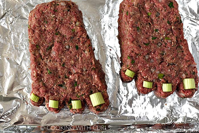 Meatloaf formed into the shape of two feet with four toes and celery pieces as toe nails on a foil lined baking sheet.