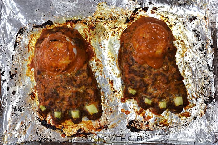 Two feet loafs baked with brushed on barbecue sauce on a foil lined baking sheet.