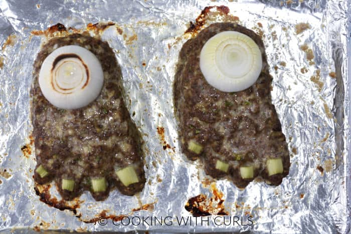 Two feet loafs with onion ring stump and celery toe nails on a foil lined baking sheet.