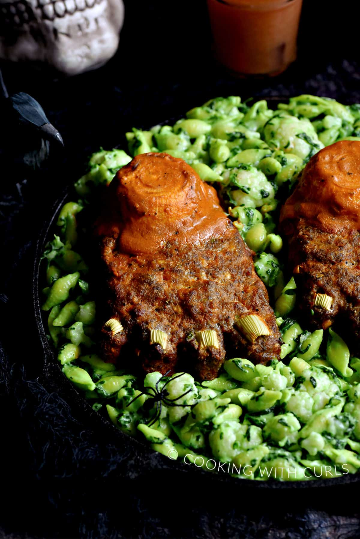 Two feet shaped meatloaves on a bed of green mac and cheese.