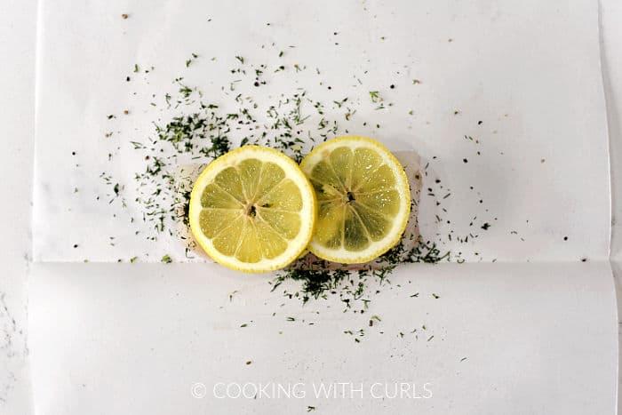Two lemon slices on top of the seasoned cod filet.