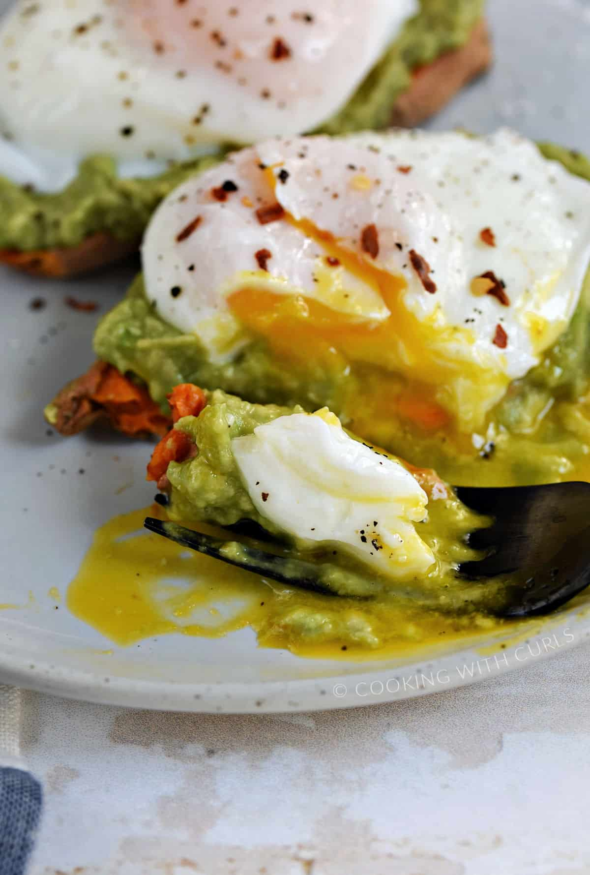 A fork sliced through the poached egg, avocado, and sweet potato and resting on a plate.