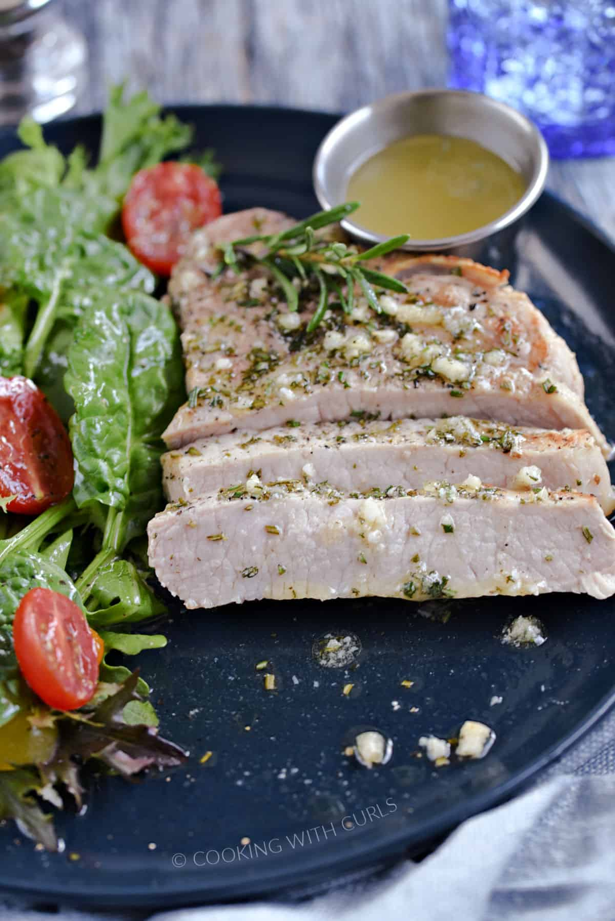 A sliced pork chop topped with melted garlic rosemary butter with a green salad on the side.