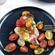Cod filet topped with cherry tomato halves, strips of basil, red onion and black pepper with title graphic across the top.