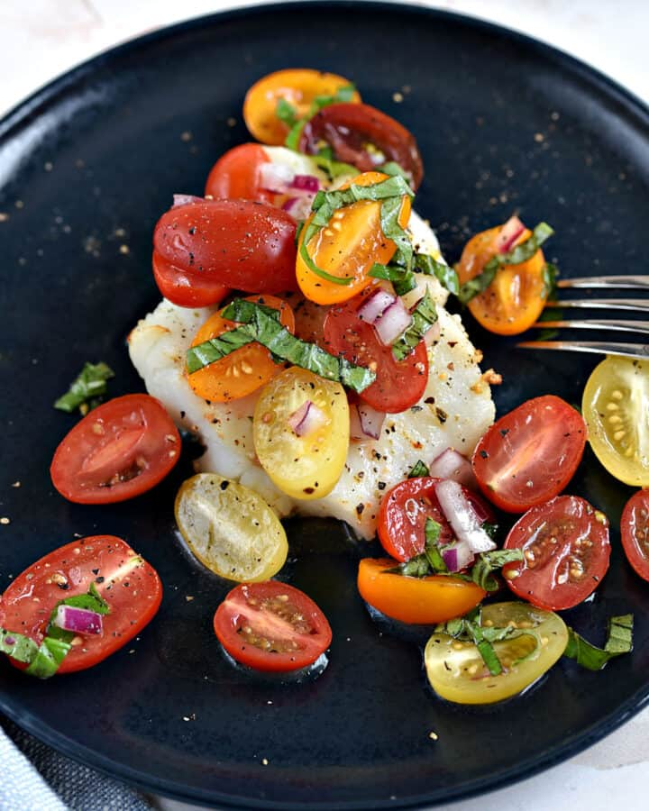 Cod filet topped with cherry tomato halves and strips of fresh basil.
