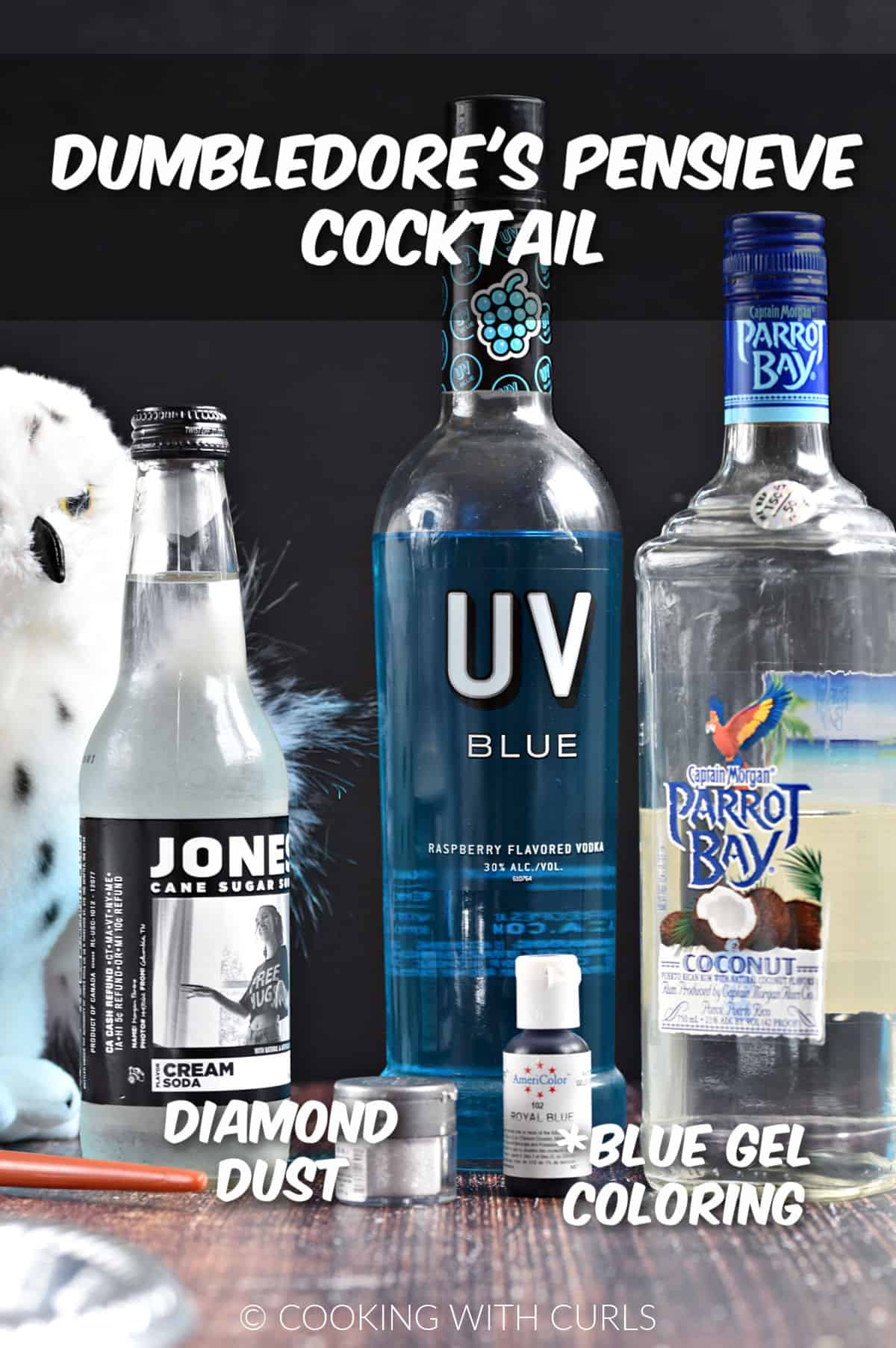Bottles of cream soda, blue vodka, coconut rum, blue coloring, and diamond dust glitter with a stuffed owl and wand in the background.