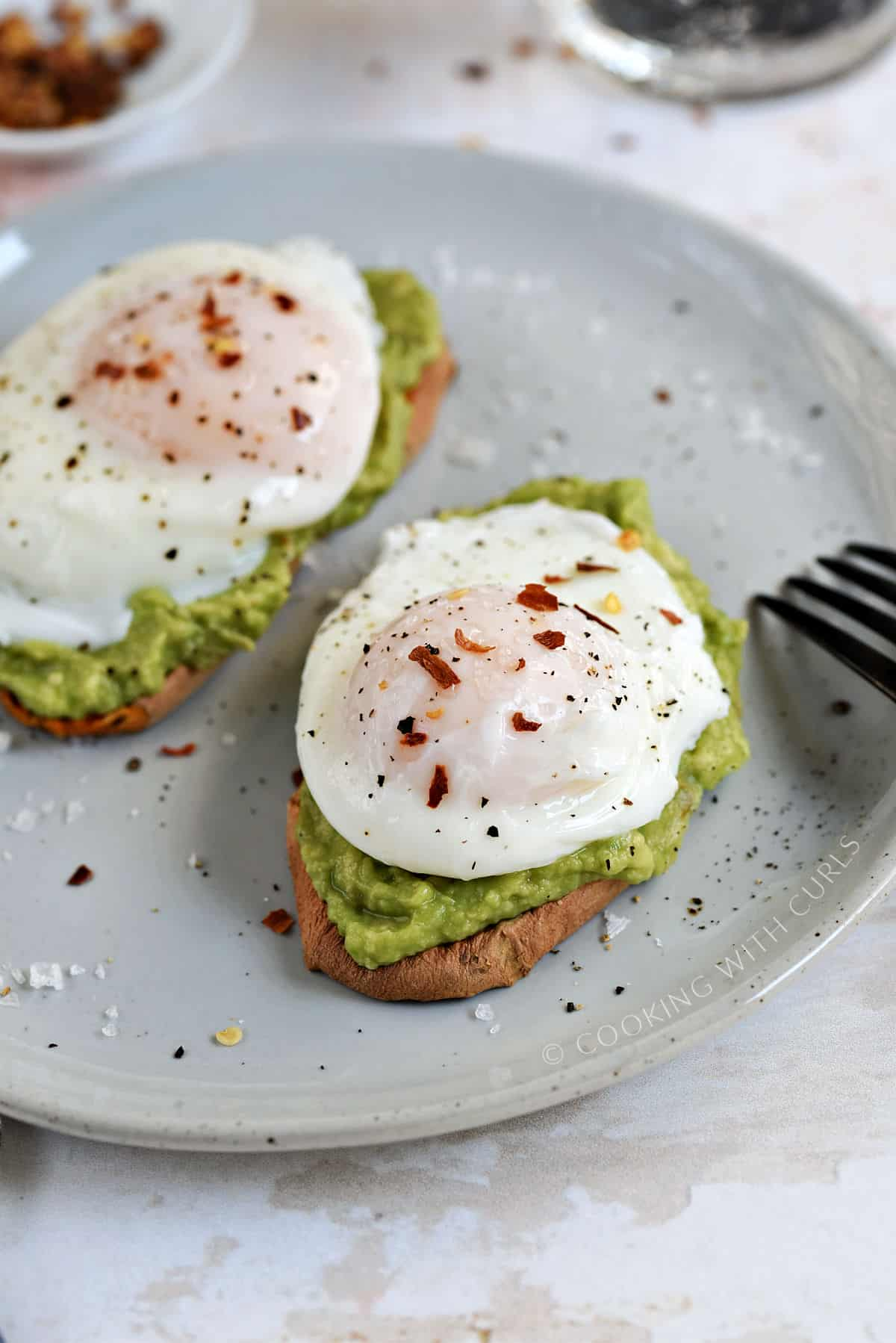 Close-up image of two poached eggs sprinkled with red pepper and salt flakes on avocado toast.