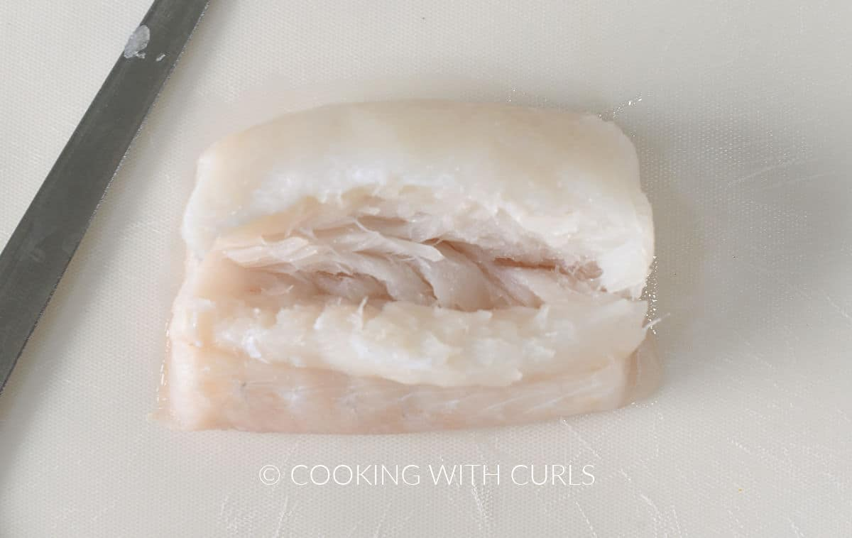 Cod filet with a slit cut down the center.
