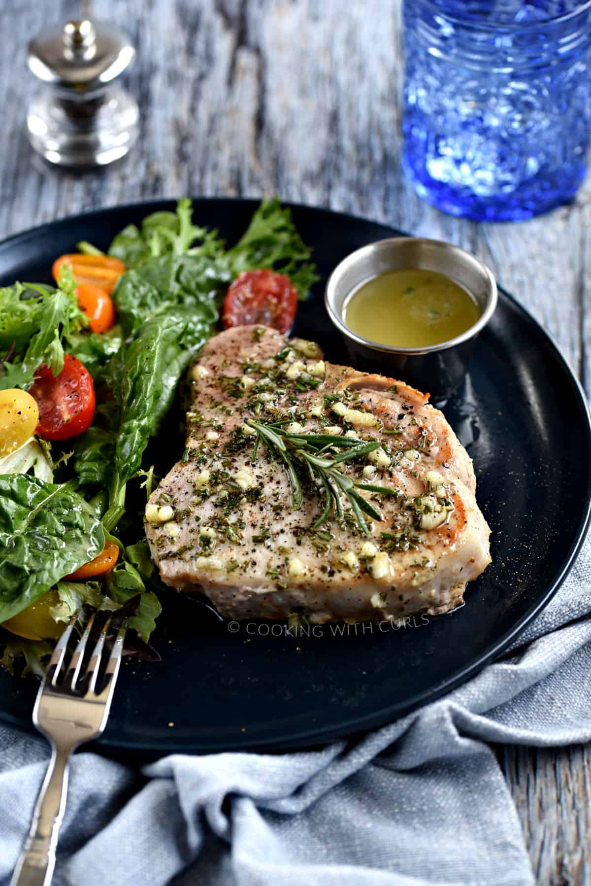 Thick, bone-in pork chop topped with garlic-rosemary butter with a green salad and cherry tomatoes on the side.