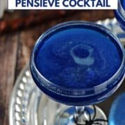 Swirling, shimmering blue drink in a coupe cocktail glass sitting on a silver tray with a spider on the base with title graphic across the top.